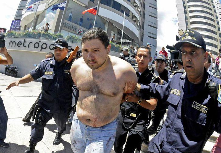 Rigoberto Paredes, con manchas de sangre en el cuerpo y esposado es escoltado por la policía en Tegucigalpa, Honduras, tras apuñalar a un abogado que representaba a un funcionario acusado de vender medicamentos fraudulentos al gobierno. (Agencias)