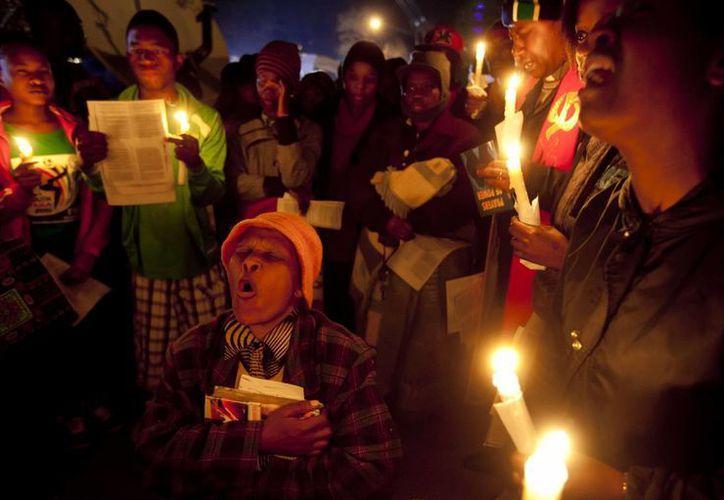 Cientos de personas hacen guardia y oración ante el hospital de Pretoria, Sudáfrica, por la salud de Mandela. (Agencias)