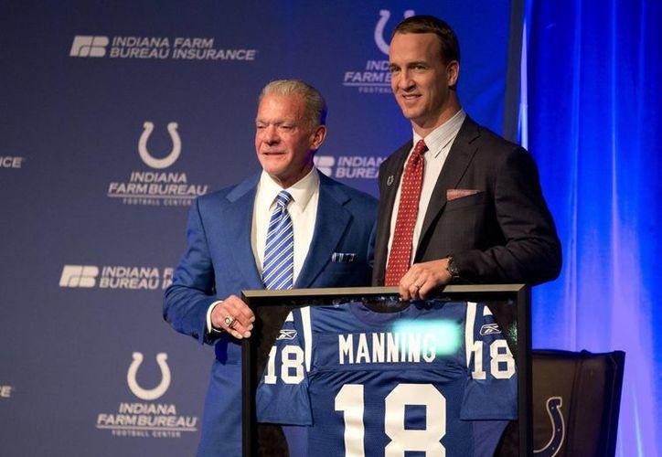 En la foto, el propietario del equipo, Jim Irsay(i) hace entrega del jersey que utilizó Peyton Manning, con los Potros de Indianapolis. (AP)