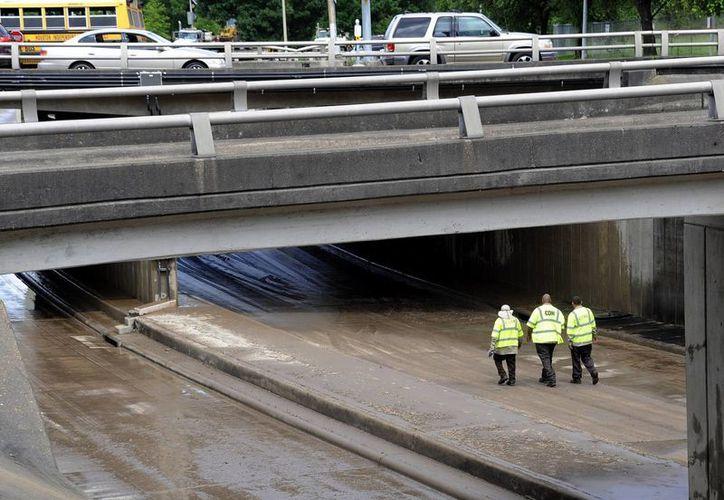Trabajadores inspeccionan este 27 de mayo de 2015 un paso a desnivel en una autopista del centro de Houston, Texas, que fue cerrada por las inundaciones causadas por las lluvias. (Foto: AP)