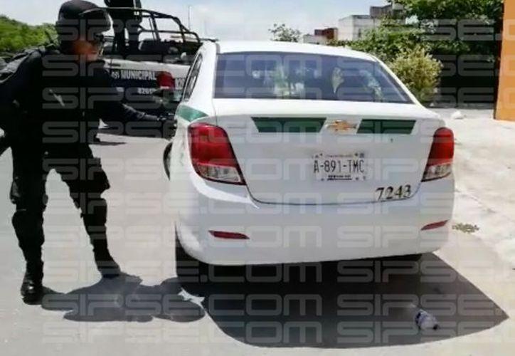 El taxi en el que viajaban los presuntos asaltantes fue asegurado por los elementos policíacos. (Redacción)