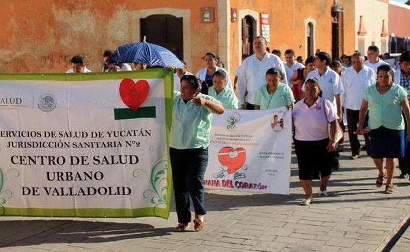 Madres de familia desfilan con el estandarte del Centro de Salud. (SIPSE)