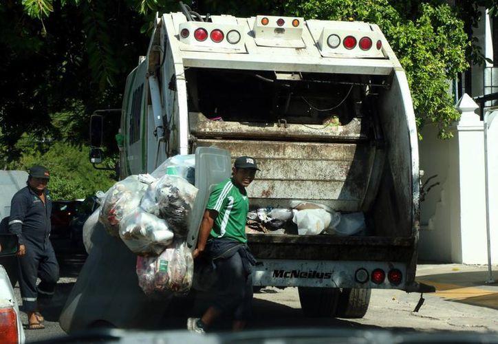 Los usuarios podrán tener mayor acceso al servicio y horario de recolección de basura. Imagen de contexto dos empleados de un camión recolector de desperdicios. (Milenio Novedades)