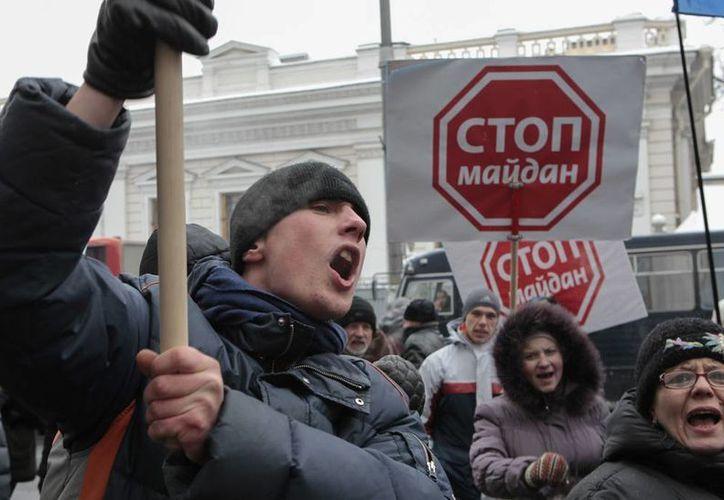 El primer ministro de ese país, Mykola Azarov renunció a su cargo como una medida para aplacar las protestas contra el Gobierno. En la imagen, ciudadanos protestan en las calles de Kiev, Ucrania, país sacudido por las manifestaciones públicas en contra del actual gobierno. (Agencias)