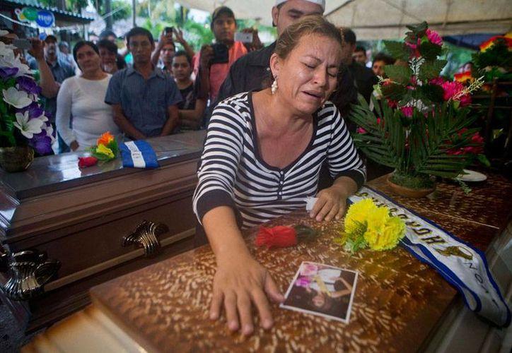 Teresa de Jesús Muñoz, madre de María José Alvarado, Miss Honduras 2014, llora en el féretro de su hija. La reina de belleza perdió la vida a manos del novio de su hermana Sofía. (AP)