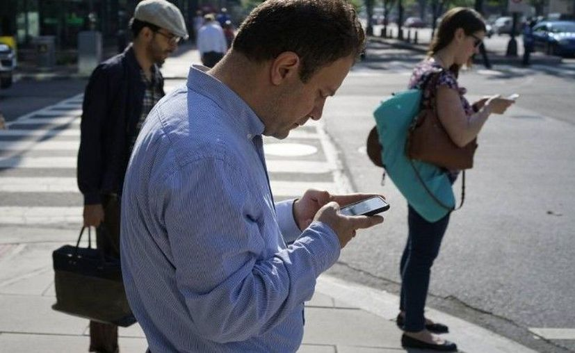 Un ejemplo de alucinación invertida es el uso consciente de un teléfono móvil en situaciones de riesgo, como cruzar la calle. (Foto: contexto Internet)