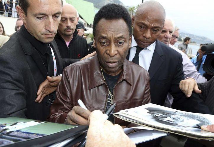 Joshua Nascimento sigue con el legado de su padre, el exfutbolista 'Pelé', quien aquí sale firmando autógrafos. (EFE/Archivo)