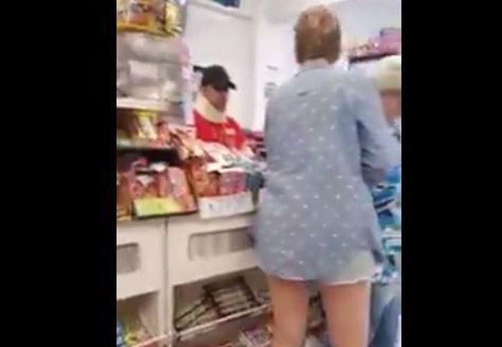 La mujer aventó dulces y productos que tenía a su alcance a los empleados. (Foto: Captura/YouTube)