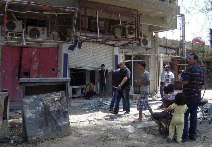 Varios ciudadanos iraquíes contemplan el lugar donde un artefacto explotó, en el céntrico barrio de Al Karrada, en Bagdad. (Archivo/EFE)