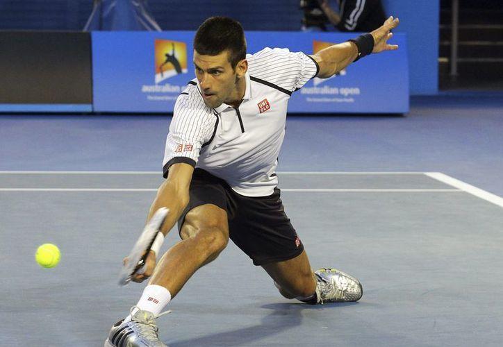El tenista serbio Novak Djokovic golpea la bola ante el checo Tomas Berdych durante su encuentro de los cuartos de final del Abierto de Australia. (EFE)