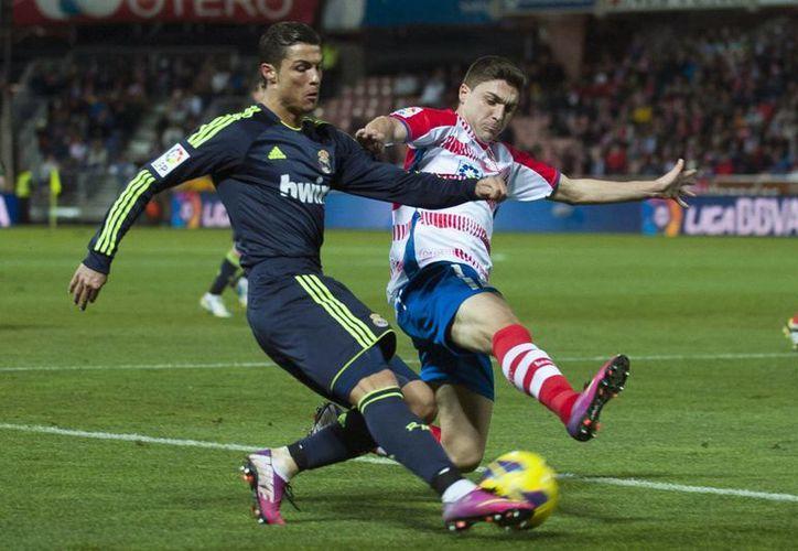 El 'merengue' Cristiano Ronaldo compite por el balón con Guilherme Siqueira del Granada. (Agencias)
