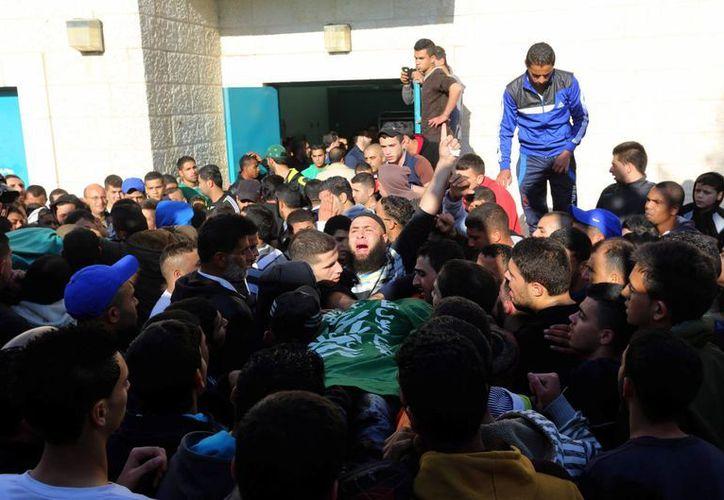 Un grupo de palestinos llevan los cuerpos de sus compatriotas muertos. (EFE)