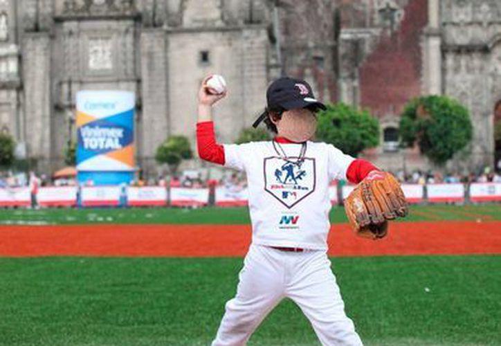 Este viernes se abrió el improvisado parque de beisbol en la 'plancha' del Zócalo del Distrito Federal, en donde se celebra el Derby de Jonrones 2015. Imagen de uno de los niños que participó en las prácticas de este viernes. (Notimex)