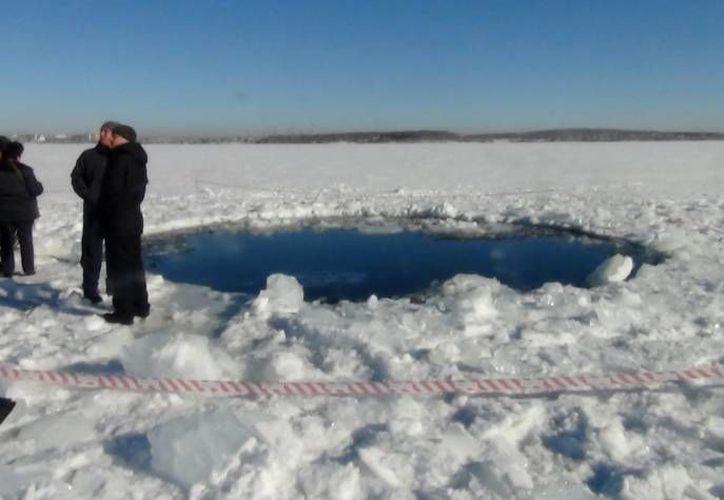 Investigadores y fuerzas de seguridad aún estudian la zona donde cayó el meteorito. (Agencias)
