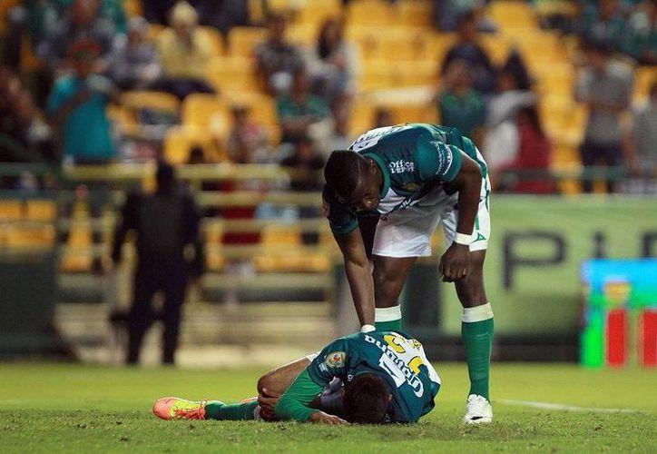 León cayó 1-3 ante Pachuca ayer en el Nou Camp. En la imagen, Mauricio Castaneda (en el césped) se duele de un golpe ante la mirada 'consoladora' de Franco Arizala. (Agencias)