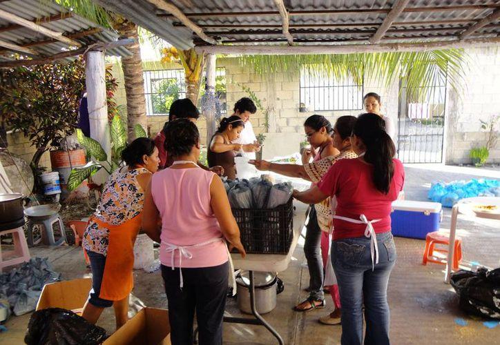 Es el cuarto año que un grupo las familias se une para llevar comida a la mesa de los habitantes de zonas marginadas. (Cortesía/SIPSE)