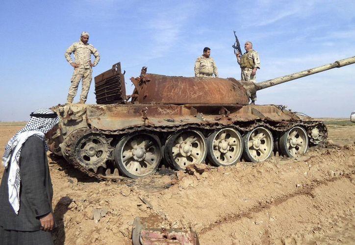 Varios soldados iraquíes permanecen de pie sobre un tanque abatido durante los enfrentamientos con las milicias del Estado Islámico (EI) cerca de Tikrit, capital de la provincia de Saladino, Irak. (Arcivo/EFE)