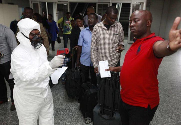 Un trabajador de servicios sanitarios examina con un termómetro a un viajero en el Aeropuerto Internacional Murtala Muhammed, en Lagos, Nigeria, para descartar que esté infectado de ébola. (Foto: AP)