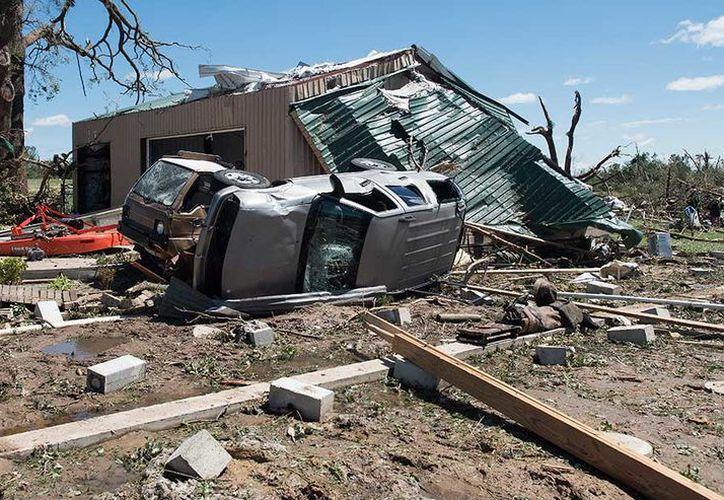 El fenómeno también dejó autos volteados y casas de dos pisos destruidas. (Foto:AP)