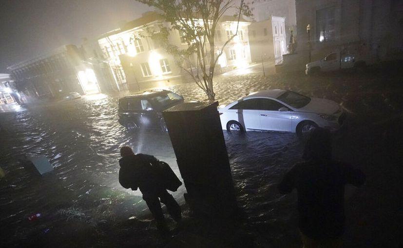 Una persona usa una linterna mientras camina por calles inundadas en busca de su vehículo, la madrugada, en Pensacola, Florida. (AP Foto/Gerald Herbert)