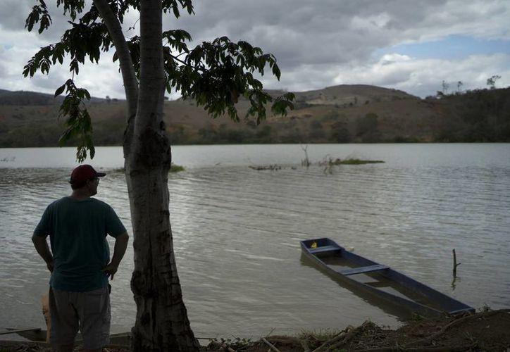 El pescador Deucimar Teixeira Lordes, de pie en la orilla del río Doce, en Mascarenhas, Brasil. Deucimar duda que vuelva a pescar alguna vez en el Doce, debido al enorme tsunami de lodo contaminado que ocurrió hace un año. (AP/Leo Correa)