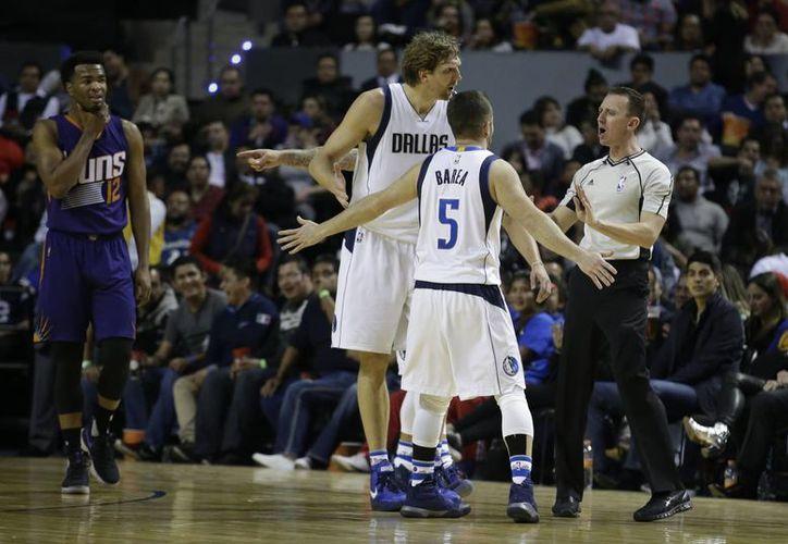 J.J. Barea (5) y Dirk Nowitzki, de Mavericks, discuten con un árbitro mientras Suns TJ Warren observa. En juego disputado en la Ciudad de México. (AP)