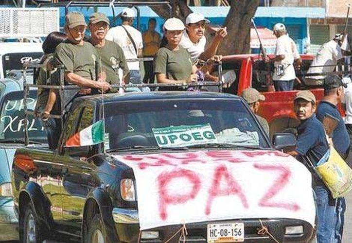 A la cabeza de la marcha, una bandera de la Upoeg. (Milenio)