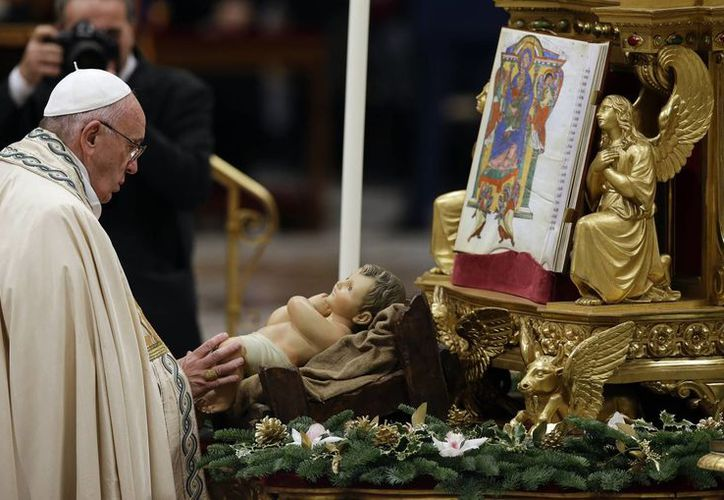 El Papa Francisco ante una imagen del Niño Jesús ubicada a los pies del altar mayor en la Basílica de San Pedro, previo al Te Deum de acción de gracias por el año 2015. (AP)