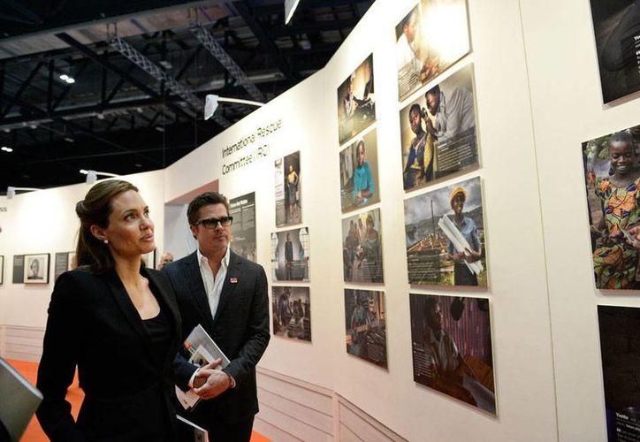 Los actores Brad Pitt y Angelina Jolie observan fotografías en una exposición sobre violencia sexual durante las guerras. (AP)