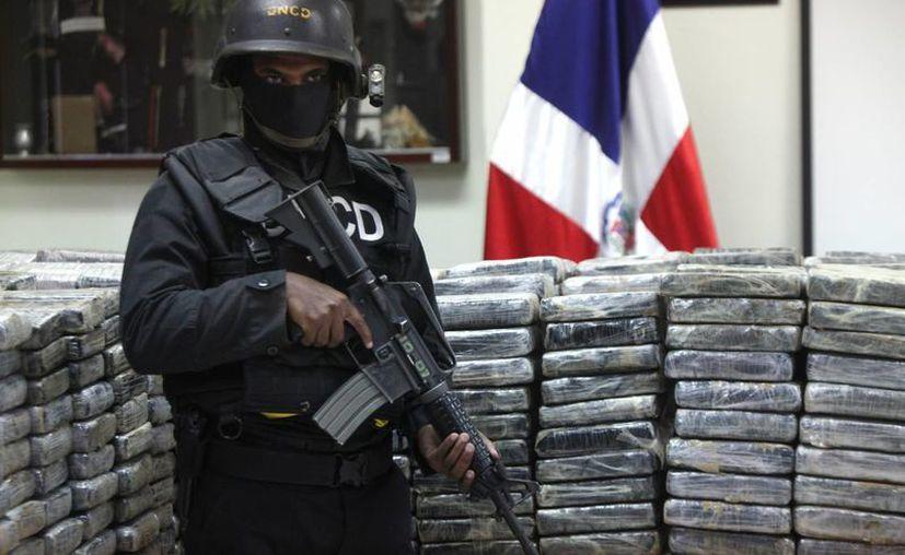Agentes de la Dirección Nacional de Control de Drogas custodian unos 1,900 kilos de cocaína. (EFE)