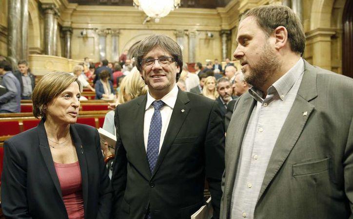 La presidenta del Parlamento catalán, Carme Forcadell, el presidente del gobierno catalán, Carles Puigdemont (c), y el vicepresidente, Oriol Junqueras (d), en el hemiciclo de Barcelona tras aprobarse el referéndum independentista. (EFE)