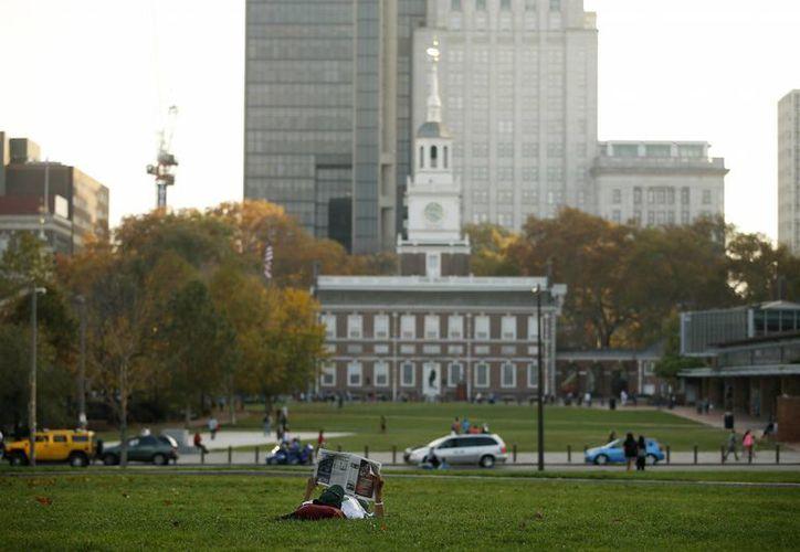 Un hombre lee el periódico frente al Independence Hall, el viernes 6 de noviembre de 2015, en Filadelfia. La ciudad fue nombrada Patrimonio Mundial el viernes. (AP Photo/Matt Slocum)