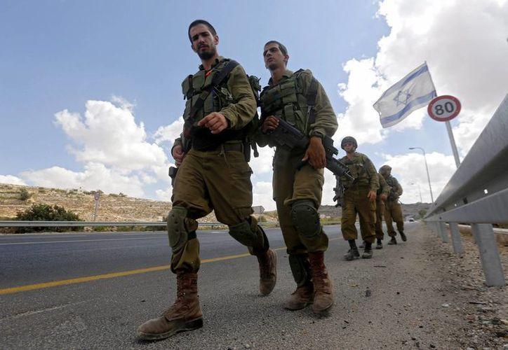 Varios miembros del ejército israelí hacen guardia cerca del lugar donde se ha producido una tentativa de apuñalamiento por un jóven palestino en la entrada de la comunidad de Kiriat Arbá en Hebrón, Palestina. (EFE/Archivo)