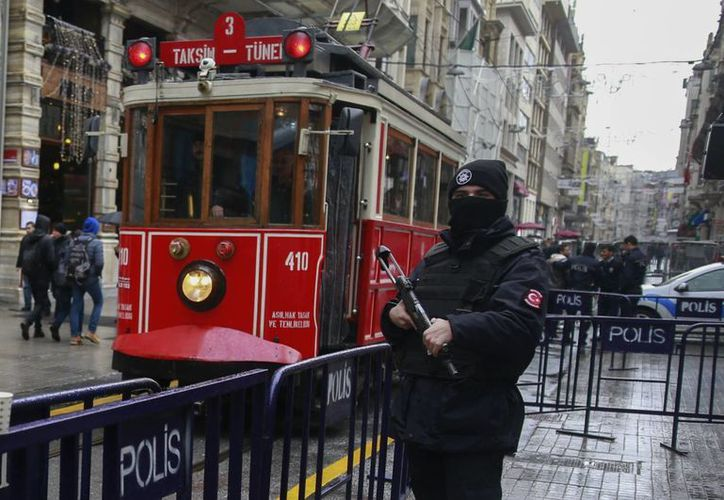 Un tranvía pasa junto a un oficial de policía turco que vigila la principal calle comercial de Estambul tras el ataque cometido en diciembre pasado. (AP/Emrah Gurel)