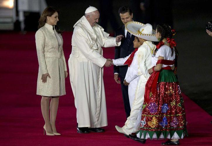 Varios artistas muy conocidos en México como Diego Verdaguer y Belinda acudieron al  hangar presidencial por la llegada del Papa Francisco, quien en la foto saluda a dos niños mexicanos vestidos con trajes típicos. (AP)