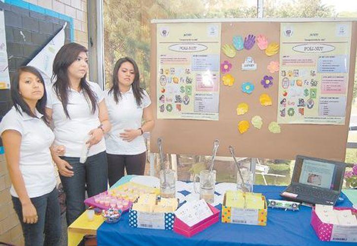 Tres de los seis estudiantes del tercer semestre de la licenciatura en alimentos muestran el proyecto. (Milenio)