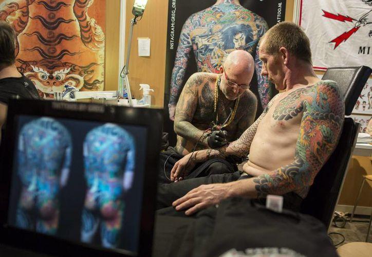 Un hombre pinta un tatuaje a otro durante la Feria Internacional del Tatuaje en París, que se celebra del 22 al 24 de marzo. (EFE)