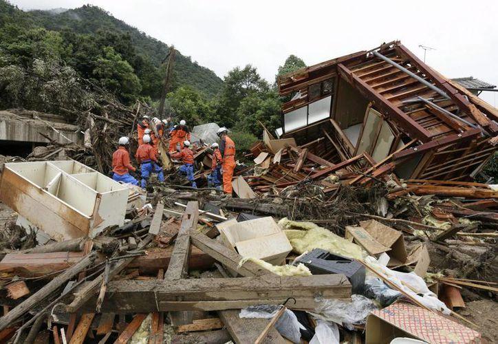Sin que las lluvias hayan parado, rescatistas realizan actividades de búsqueda y rescate de víctimas después de recientes deslizamientos de tierra en Hiroshima. (EFE)