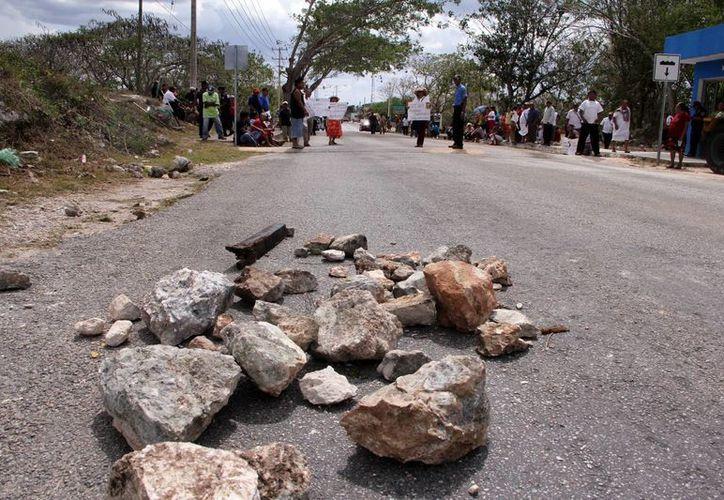 Con piedras, los manifestantes obstaculizaron el paso hacia la zona maya de Chichén Itzá. (Milenio Novedades)