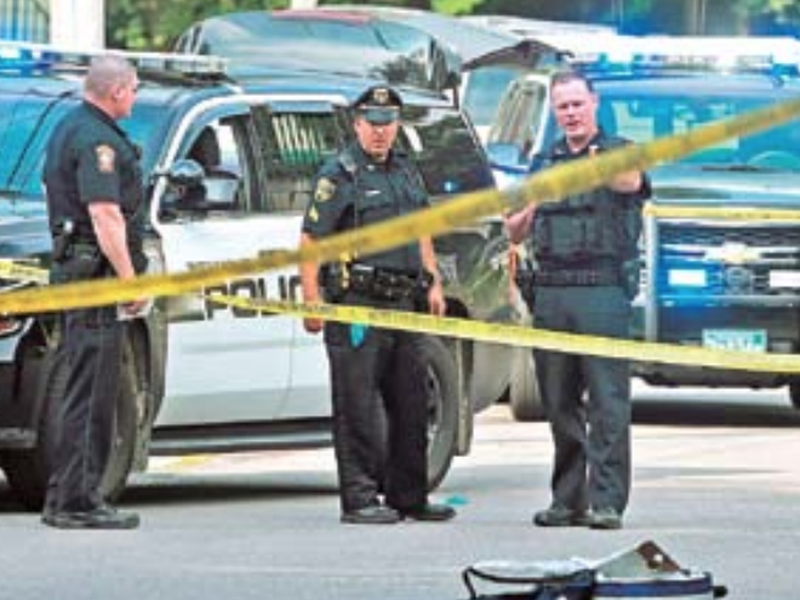 Officers work at the scene where a Weymouth police officer was shot and critically wounded while in a foot chase with a suspect following a vehicle crash, in Weymouth, Mass.