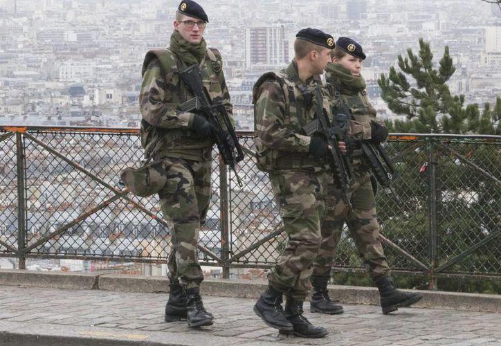 Aunque se anunció que el despliegue comenzará a realizarse este martes por la noche, ya se observan soldados en varias zonas de la capita, francesa, como este grupo, en el distrito de Montmartre. (AP/Jacques Brinon)