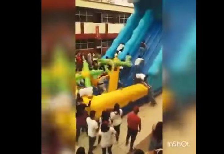 Estudiantes de la Universidad Autónoma de Tlaxcala saturaron un juego inflable, que no soportó la carga y cayó. (Impresión de pantalla)