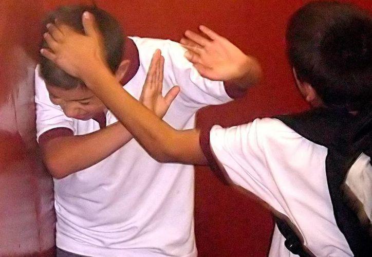 En la imagen, un menor es golpeado por uno de sus compañeros de escuela. (Milenio Novedades)