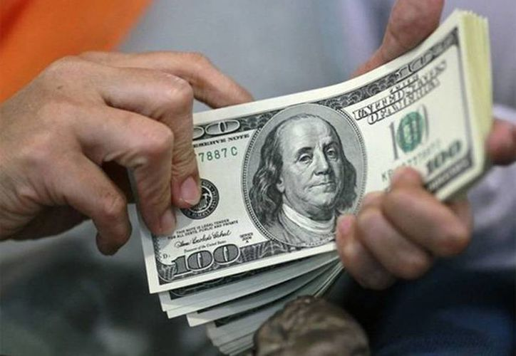 El comportamiento del dólar responde a la expectativa de una mejora en el mercado laboral estadounidense. Imagen de un hombre que cuenta unos dólares. (Archivo/SIPSE)