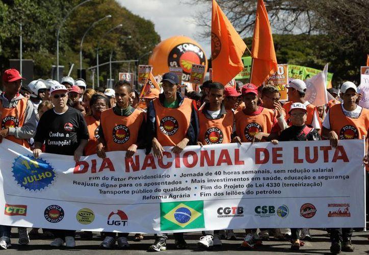Un grupo de manifestantes sostienen un cartel durante una nueva jornada de protestas en la capital Brasilia. (EFE)