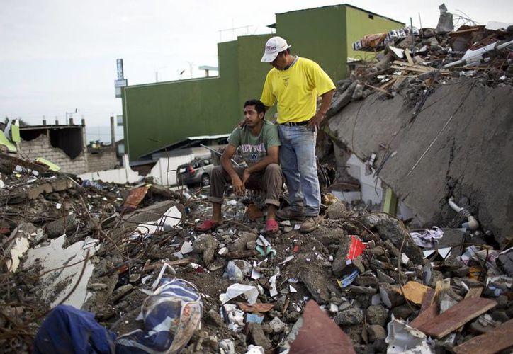 Roberto Ganchoso, sentado sobre escombros, recibe consuelo de un vecino mientras observa la demolición de un hotel contiguo a su propiedad en Pedernales, Ecuador. (Agencias)