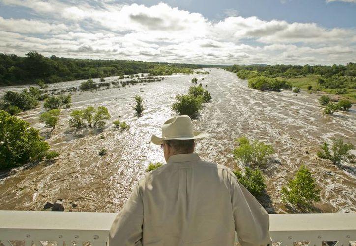 Tex Toler observa la creciente del Río Llano, en Texas, este viernes. Las autoridades monitorean el nivel de los ríos tras los diluvios del pasado fin de semana. (Foto AP/Austin American-Statesman, Jay Janner)