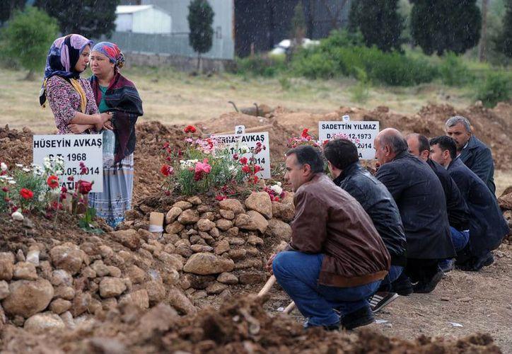 La gente reza en las tumbas de las víctimas del accidente de la mina en Soma, Turquia. (Agencias)