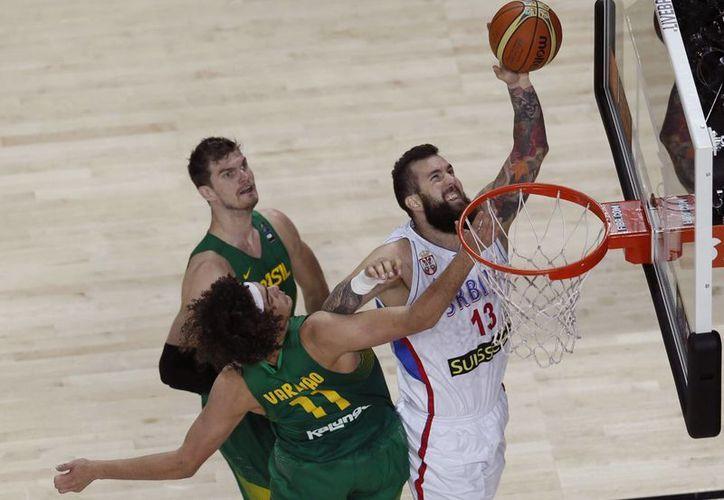 El pívot de Serbia, Miroslav Raduljica (d), intenta anotar ante los jugadores de Serbia, Tiago Splitter (i) y Anderson Varejao, durante el partido de cuartos de final del Mundial de Baloncesto 2014 en el Palacio de Los Deportes en Madrid. (EFE)