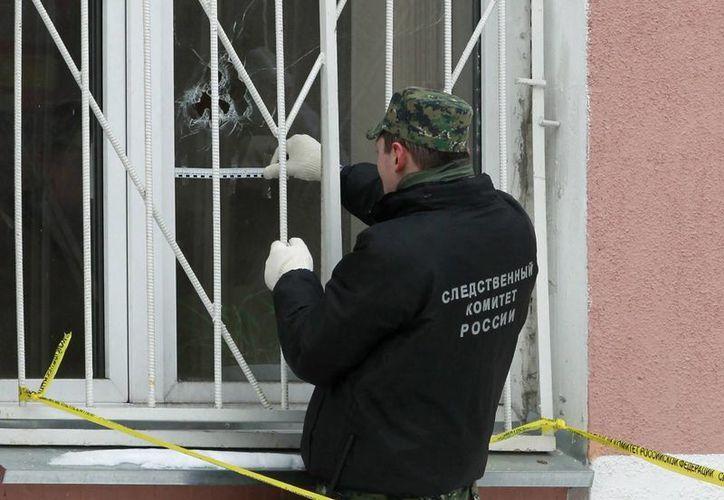 Investigadores inspeccionan el colegio que fue secuestrado por un joven armado en Moscú, Rusia. (EFE)
